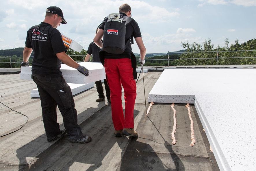 Mocowanie płyt termoizolacyjnych na dachu płaskim, z zastosowaniem kleju poliuretanowego Soudatherm Roof. Fot. Soudal
